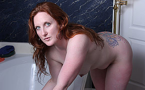 Sexy American redhead enjoys her toy in the bathtub